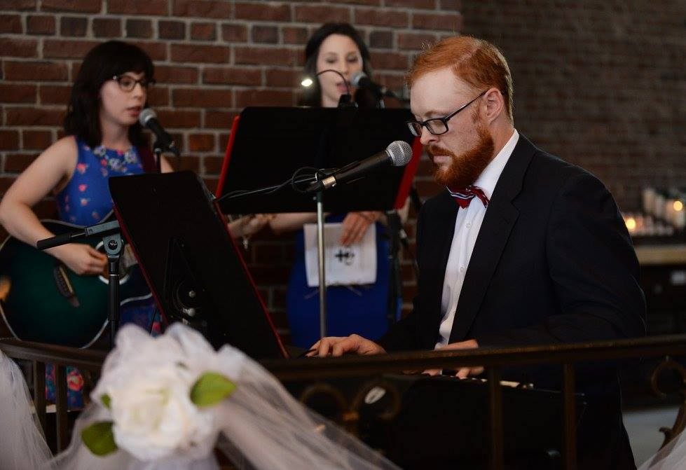 L-R: Michaela, Arianna & Joe, playing in St. Maurice's choir space for the Haggart wedding in August of 2016. Joe is sporting a slick bowtie and his beard looks particularly red as he plays the keys. Michaela is strumming guitar and singing. Arianna is singing too.