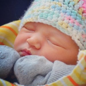 a beautiful close-up of my daughter very shortly after her birth in February 2016, wearing a pastel-coloured knit touque (aka the turban)